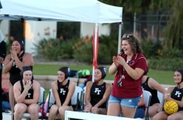 Coach Samantha Ebberson (standing) laughs with Foothill Technology's inaugural girl's water polo team. Credit: Kazu Koba/The Foothill Dragon Press