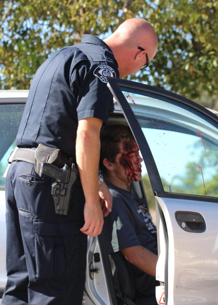 A police officer assesses Kevin Waechter's situation and how best to act by asking him questions in the typical emergency procedure. Credit: Carrie Coonan/The Foothill Dragon Press