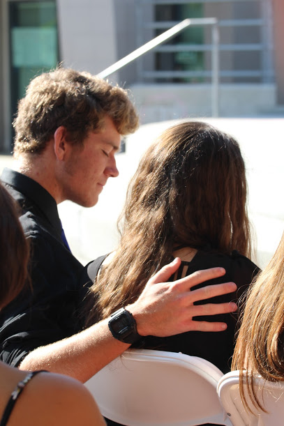 Junior Kevin Waechter comforts Senior Lauren Dalmatoff during a video honoring Chris Prewitt.  Credit: Carrie Coonan/The Foothill Dragon Press