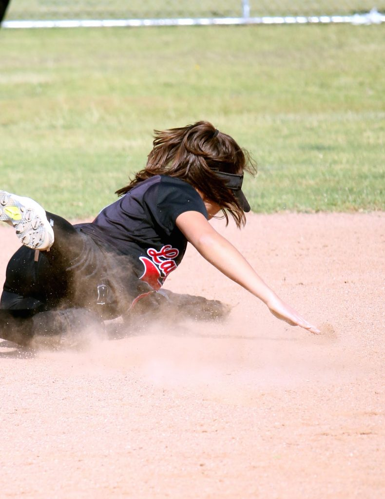 A player from Grace Brethren slides in an attempt to reach the ball.