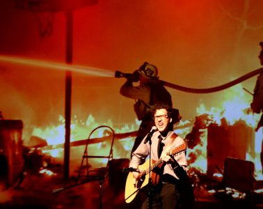 """Jake Needham sings """"My Hero"""" by the Foo Fighters standing in front of images of the Thomas Fire Firefighters. Credit: Abigail Massar / The Foothill Dragon Press"""
