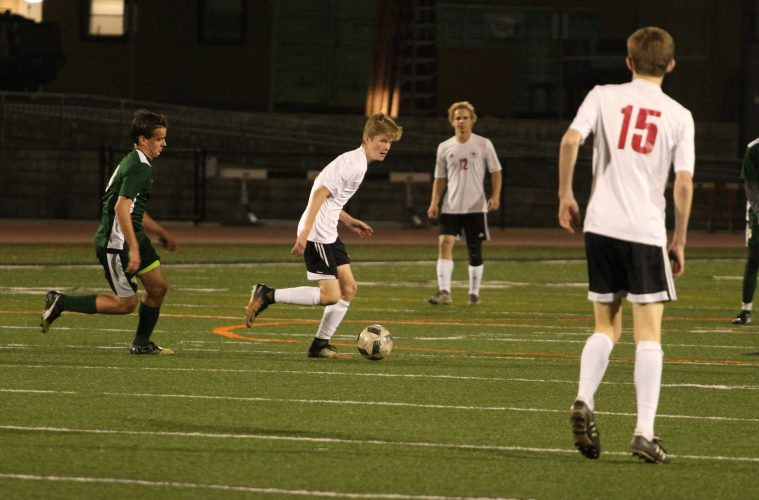 Max Turville '21 dribbles across the field looking for an open pass. Credit: Jason Messner / The Foothill Dragon Press