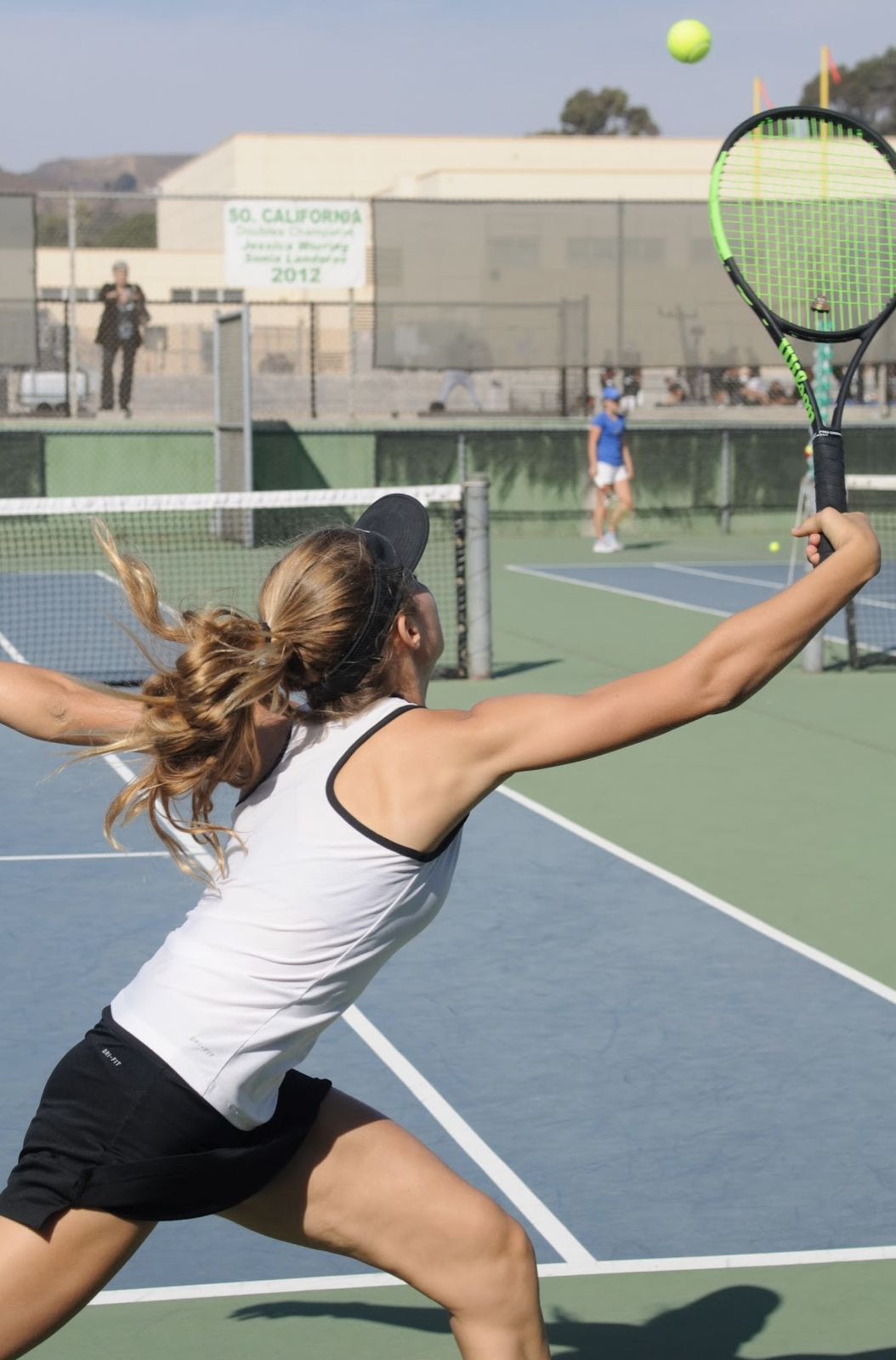 Noelle Hayward '21 reaches for the ball and manages to save it by hitting it over the net. Credit: Muriel Rowley / The Foothill Dragon Press