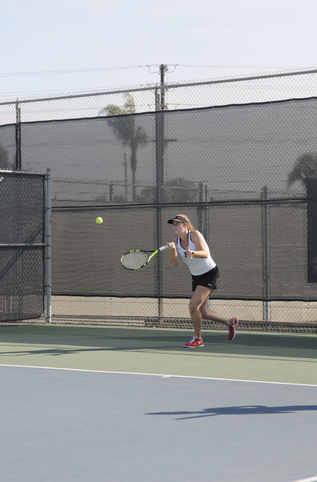 Alyssa MCLain '20 hits a ball across the net. Credit: Muriel Rowley / The Foothill Dragon Press