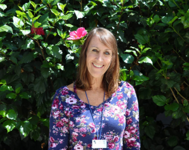 The new health technician stands in front of a wall of leaves. Credit: Olivia Sanford / The Foothill Dragon Press