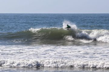 Surfer in green does a re-entry as he rides a right hander. Credit: Olivia Sanford / The Foothill Dragon Press