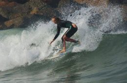 Sophie Simon '21 carves a wave, causing an ocean spray. Credit: John Simon (used with permission)