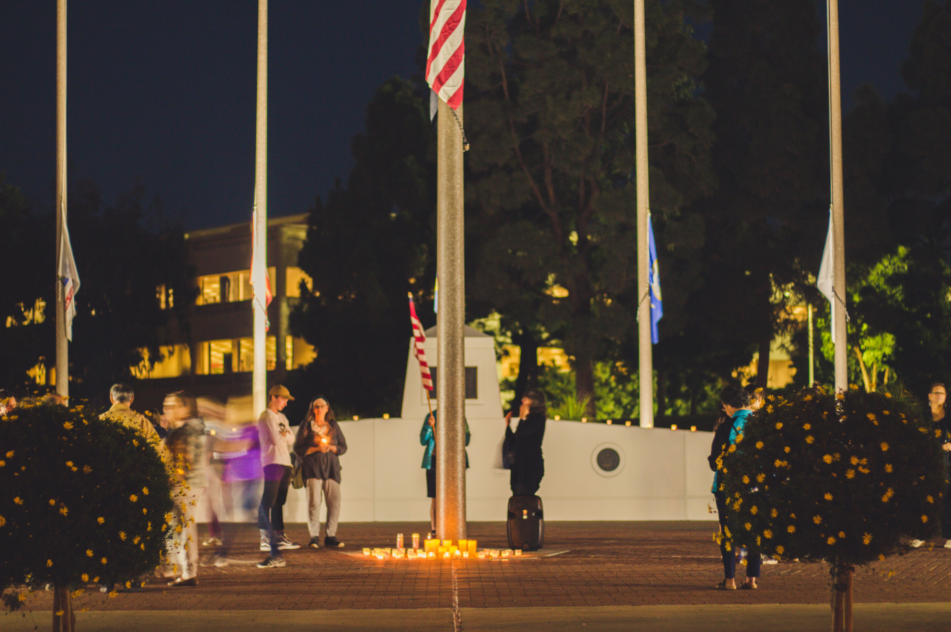 Behind the vigil, each flag hung at the government center is at half mast as a mark of respect towards each Borderline Bar & Grill shooting victim. Credit: Stefan Fahr / The Foothill Dragon Press