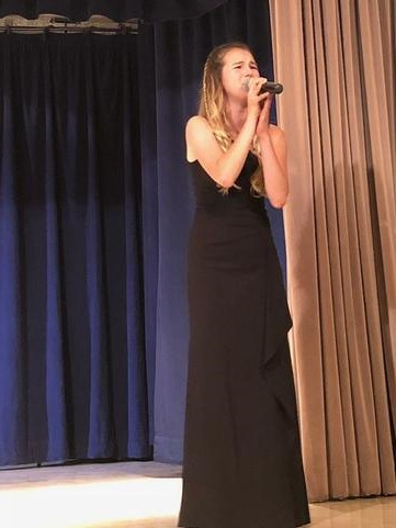 """Meghan Carter '20 takes over the stage while singing """"Lamest Place in the World"""" at the beginning of the show. Credit: Marin Valerio / The Foothill Dragon Press"""
