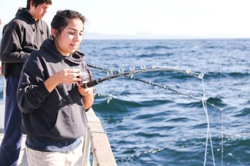 Foothill seniors Isabelle Muschamp and Luke Barnett cast lines in hopes of catching rockfish for the Biotechnology field trip. Credit: Bethany Fankhauser/The Foothill Dragon Press