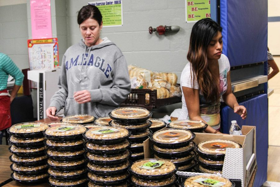 Luz Santos (right), VHS junior, assists with distributing food for Thanksgiving