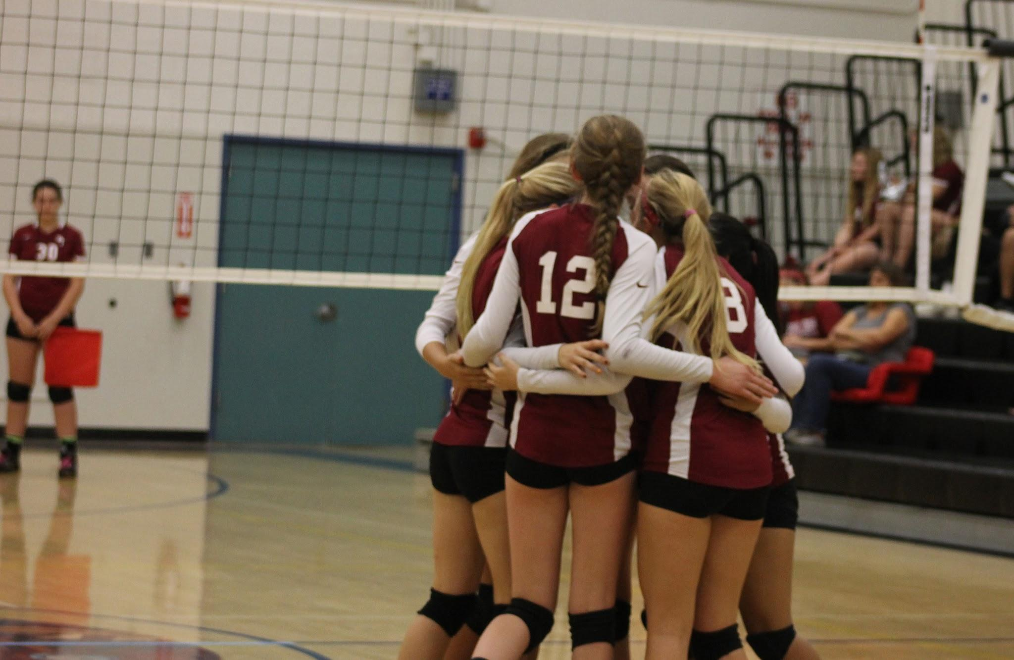The Foothill varsity girl's volleyball team hugging at their game, October 30, 2014. Credit: Elizabeth Anthony/The Foothill Dragon Press