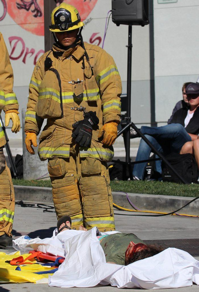 A firefighter surveys the body of senior Lauren Dalmatoff before she is placed in a body bag. Credit: Carrie Coonan/The Foothill Dragon Press