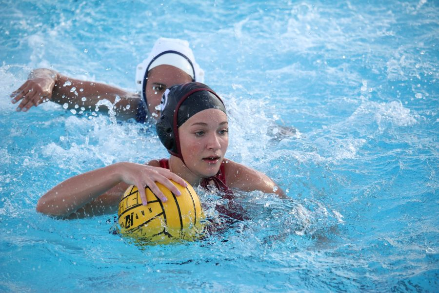Sophomore Aariana Saunders evades a [opposing team] player during the Foothill girl's water polo game Wednesday night. Credit: Grace Carey/The Foothill Dragon Press
