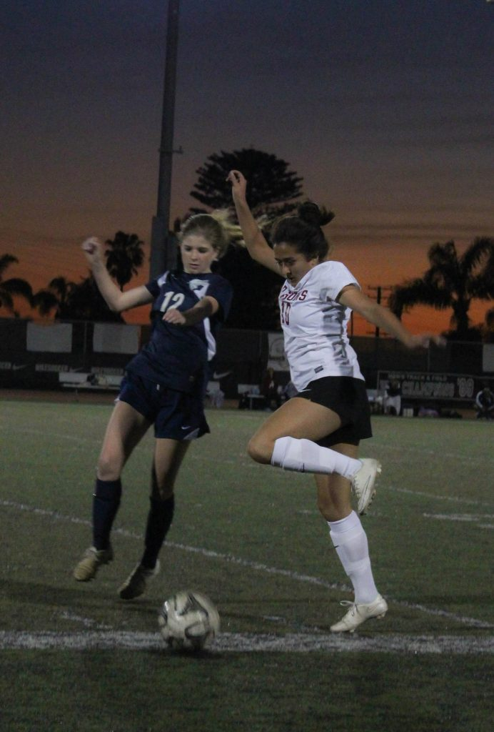 Junior Gabby Pido competes with a Villanova player for possession of the ball during Thursday night's home game. Credit: Jessie Snyder/The Foothill Dragon Press