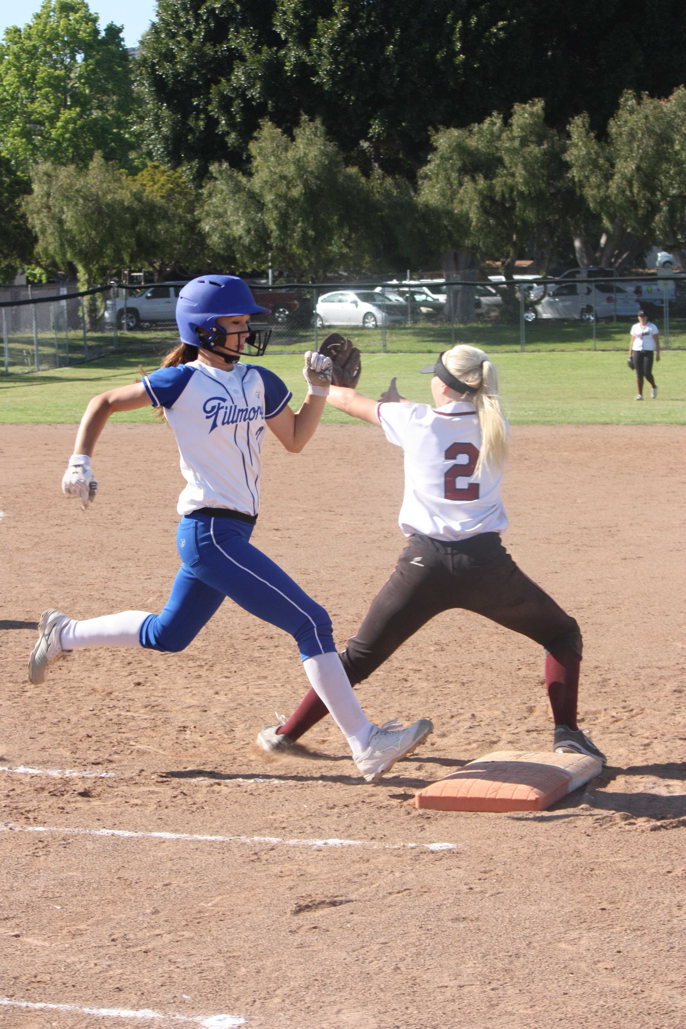 Sophomore Jamie Dietz (2) catches the ball at first base, tagging out Fillmore varsity batter. Credit: Gabrialla Cockerell/ The Foothill Dragon Press