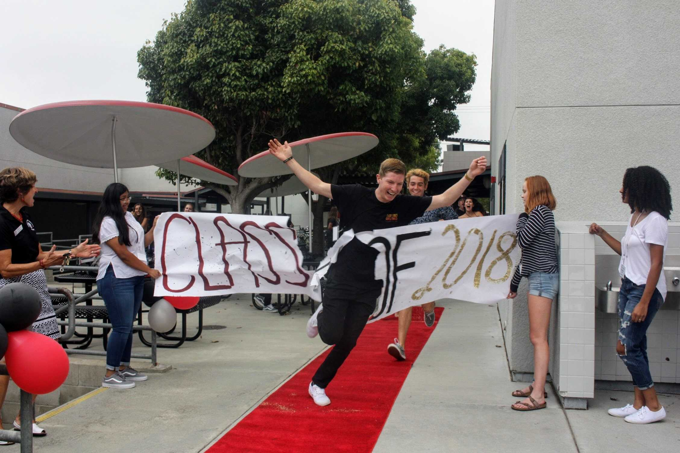 Cole Chilcutt '18 bursts through the banner on his way to the senior flash mob. Credit: Gabrialla Cockerell / The Foothill Dragon Press