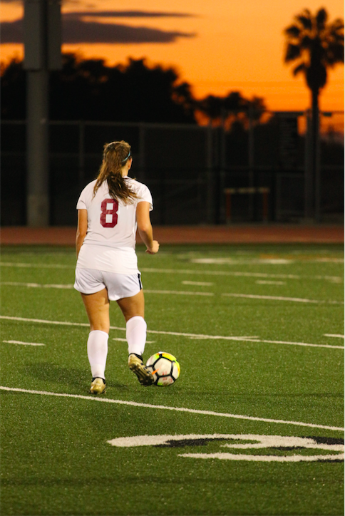 Madeleine Espinoza '20 with the ball as the sun sets in the background. Credit: Jason Messner / The Foothill Dragon Press