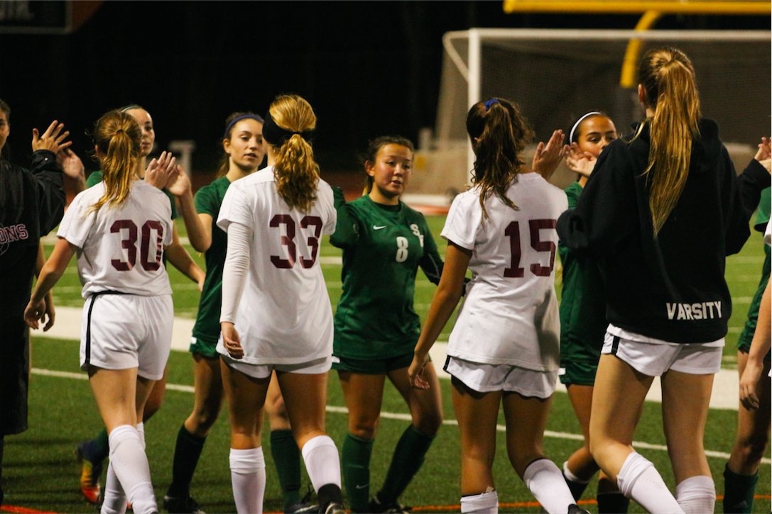 The Dragons and Seraphs exchange high-fives after a 5-0 win for the Dragons. Credit: Jason Messner / The Foothill Dragon Press