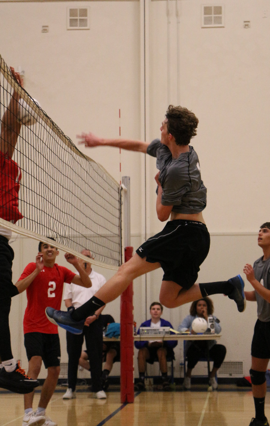 Tanner Nodolf '18 hits the ball over the net towards the blockers. Credit: Jason Messner / The Foothill Dragon Press
