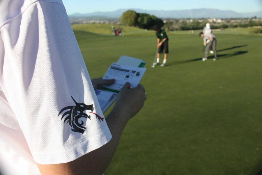 Spencer Selleck '18 records his score of the 17th hole. Credit: Gabrialla Cockerell/ The Foothill Dragon Press