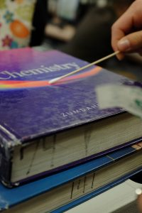 BioScience survey student swabs bacteria colony off chemistry textbook. Credit: Jason Messner / The Foothill Dragon Press