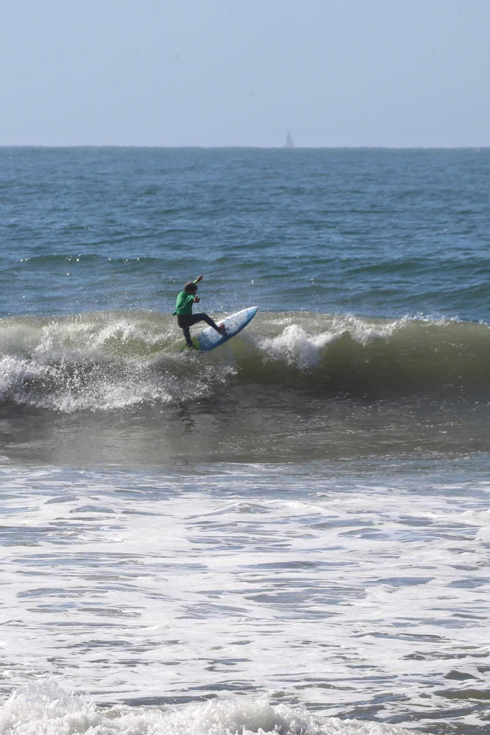 Surfer in green hitting the lip at the start of the heat. Credit: Olivia Sanford / The Foothill Dragon Press