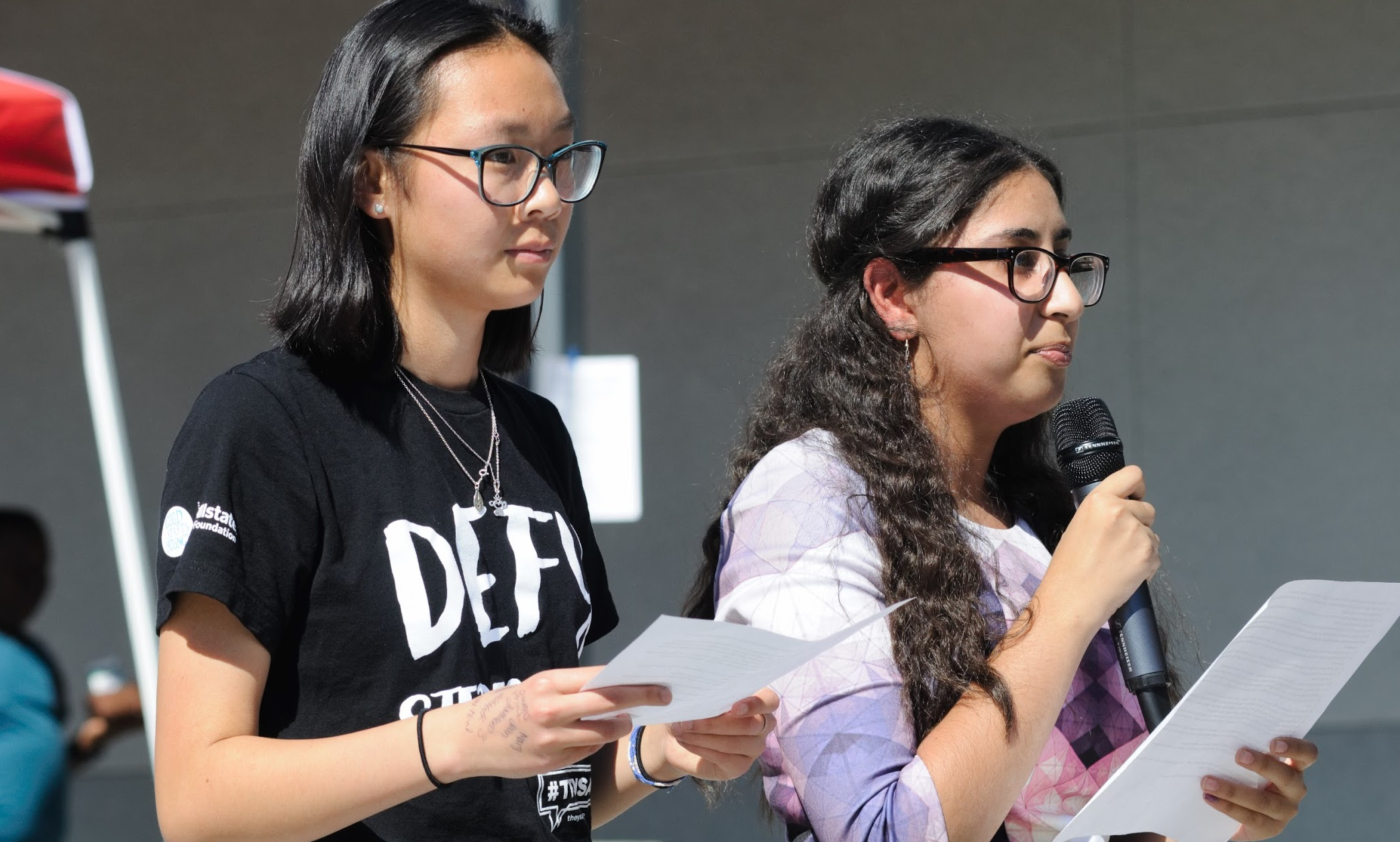 Leaders of WE Club Shealyn Massey '19 and Yoanna Soliman '19 stand on the stage and ask various questions to students that bring awareness to inequality. Credit: Muriel Rowley / The Foothill Dragon Press