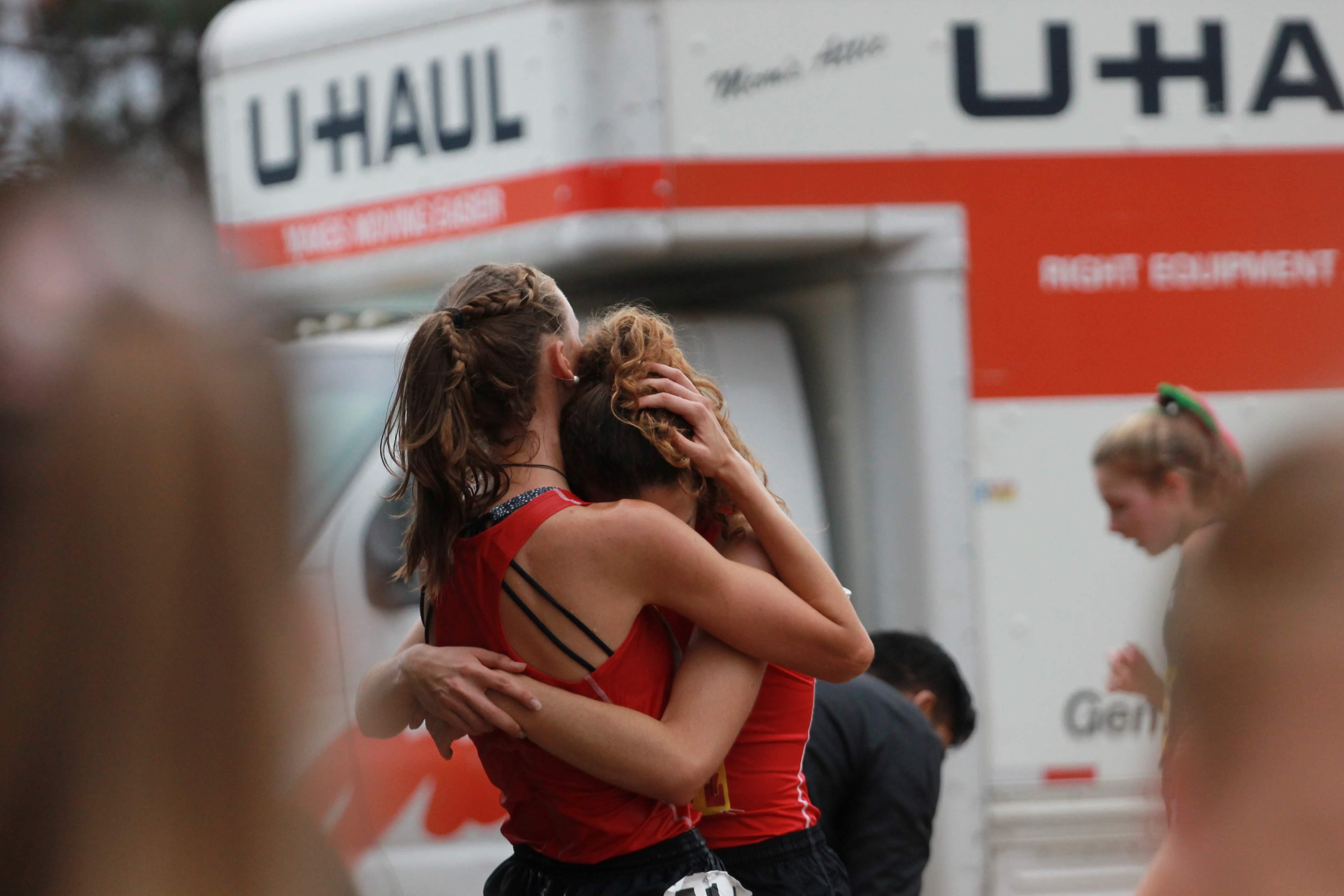 Lauren Kearney and Brooke Secreto hug after crossing the finish line. Credit: Jocelyn Brossia / The Foothill Dragon Press