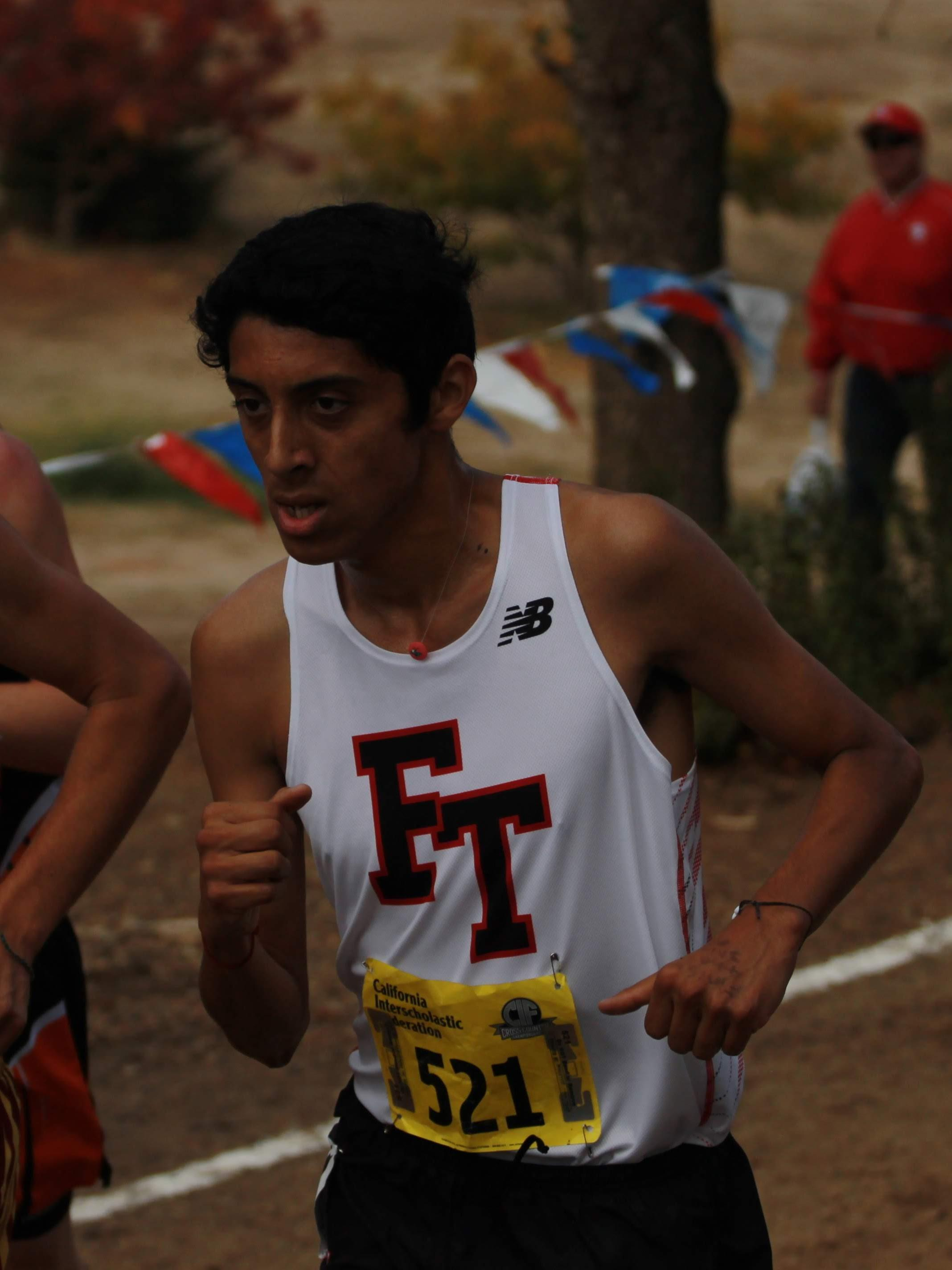 """Daniel Montes runs, wearing his necklace from the """"Buttons for Buddies"""" club. Brooke Secreto moves down a slight hill. Credit: Jocelyn Brossia / The Foothill Dragon Press"""