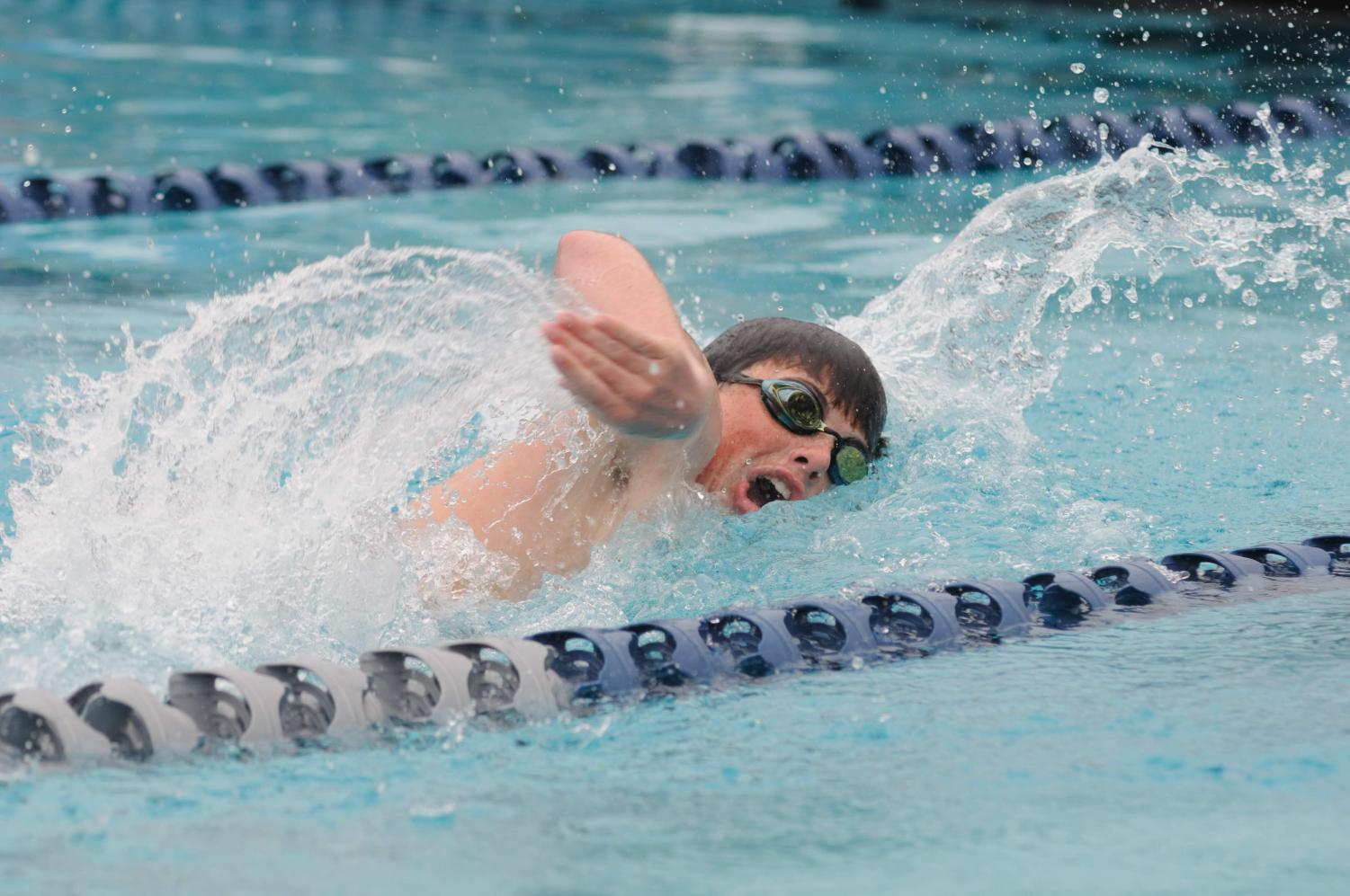 Brandon Rodgers '22 swims with speed down his lane.