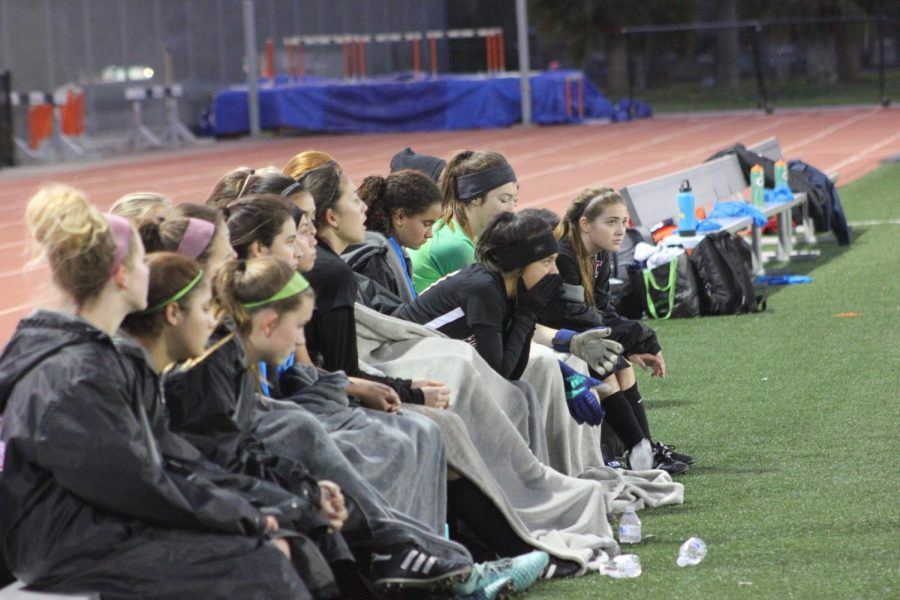 The girls listen to their coach during halftime.