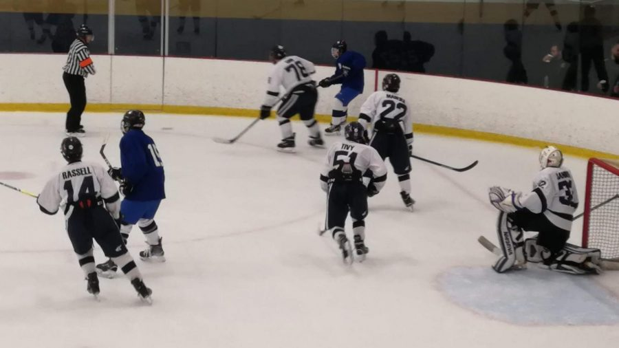 Nick Tivy '22 skates by the goalie, ready to shut down a pass across the ice.