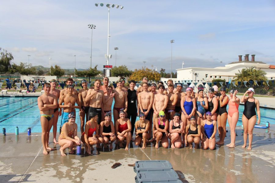 Sam Bova smiles alongside the swim team following their practice together.