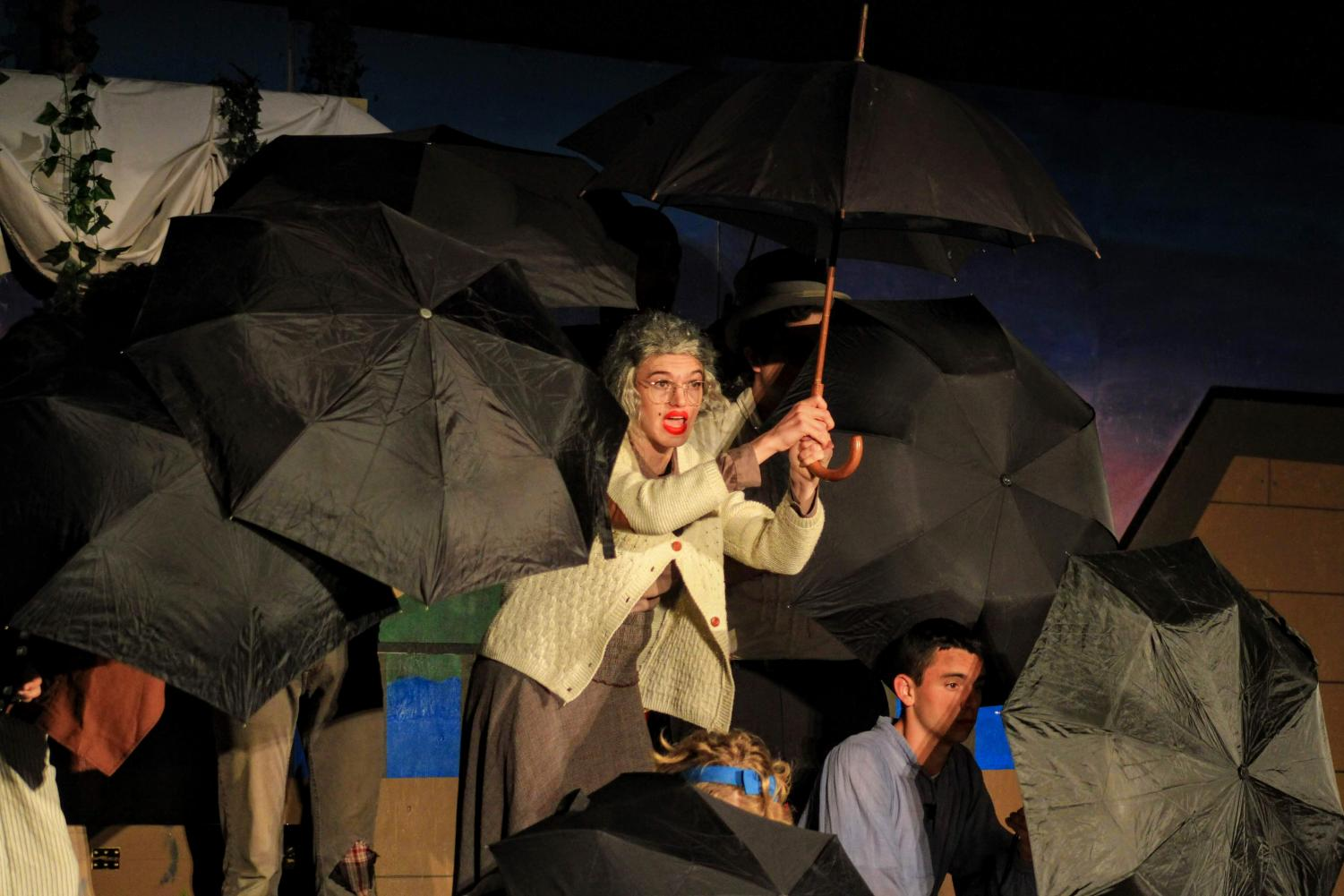 Ms.+Bumbrake+opens+her+umbrella+as+the+actors+perform+a+very+organized+skit.