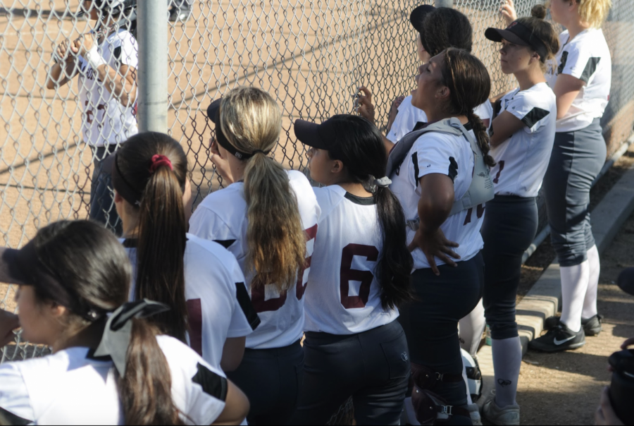 Players watch and support their teammate as they get ready to bat.