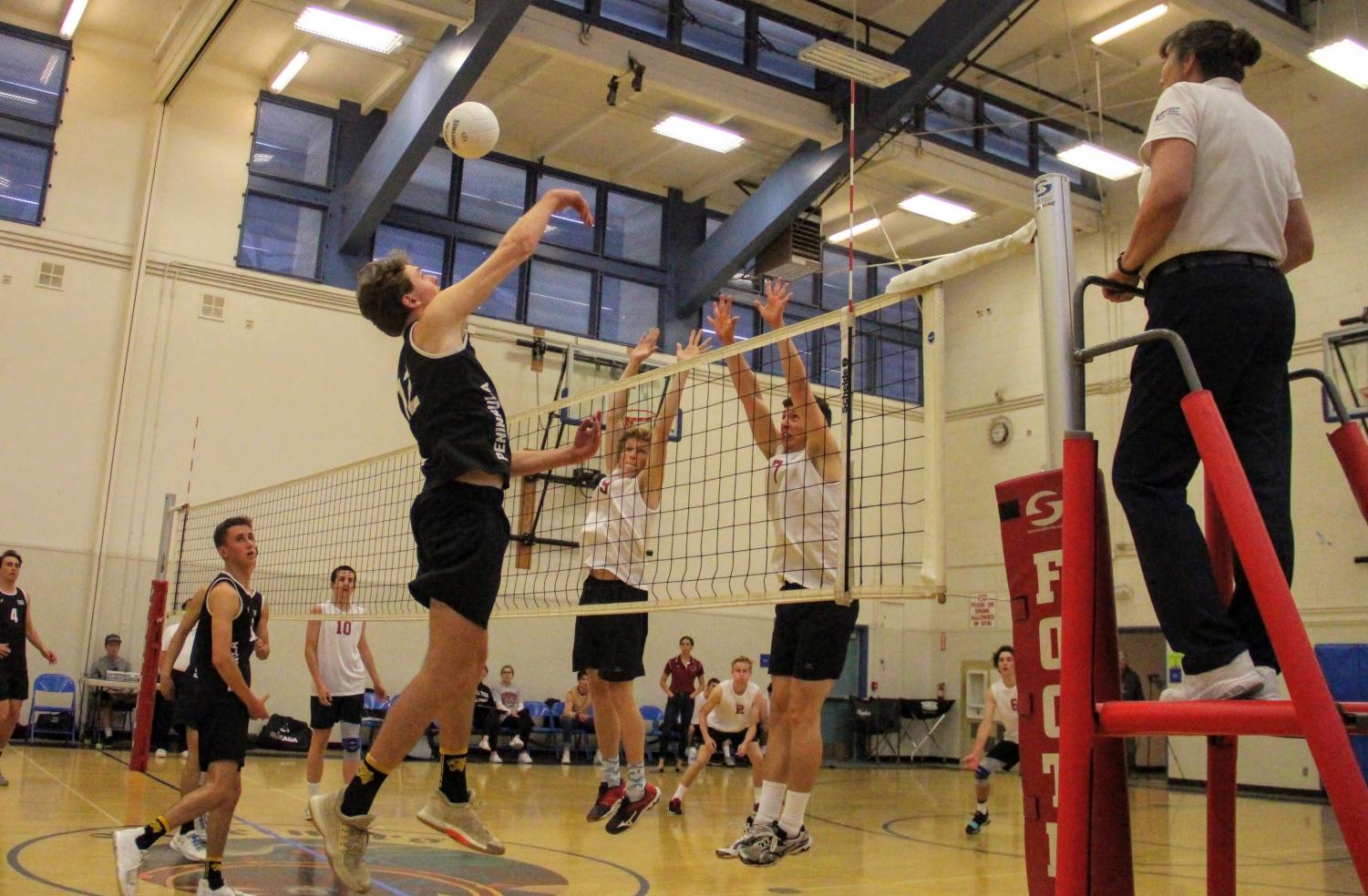Stefan Fahr '19 and Logan Grenier '19 reach up to block the incoming ball.
