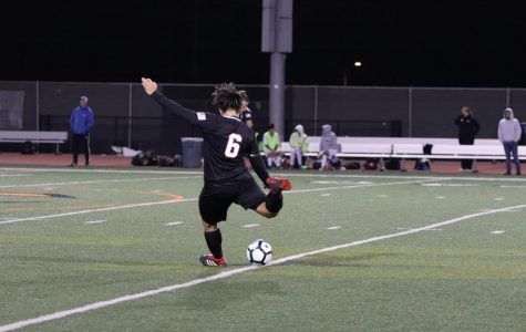 Sam Valdez '20 rears up to kick the ball up the field