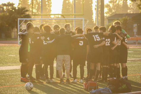 Boys Soccer team gathers with Coach Rick Villano before the game.