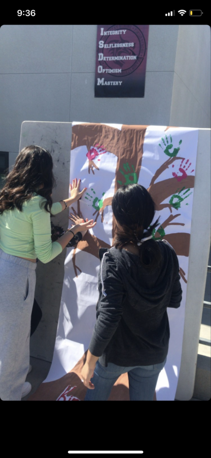 Students participate in adding their hand-print to the