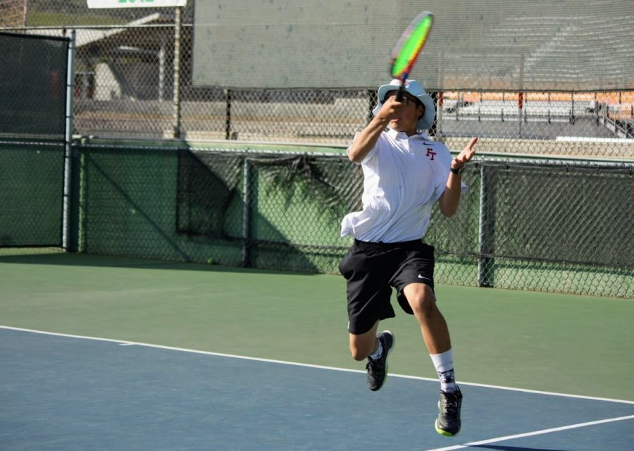 Ethan Wang '20 jumps in his forehand swing.
