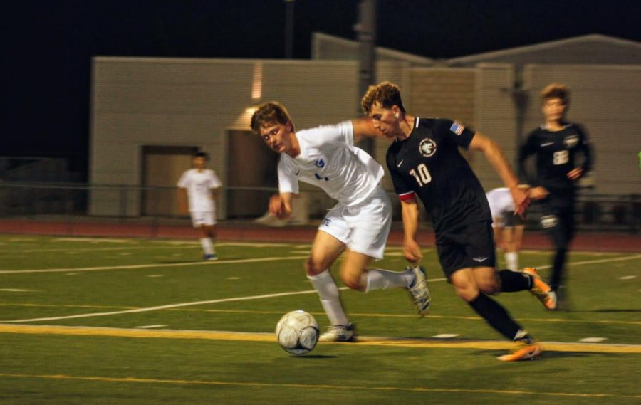 Gavin Cattanach '21 fights for the ball against his opponent.