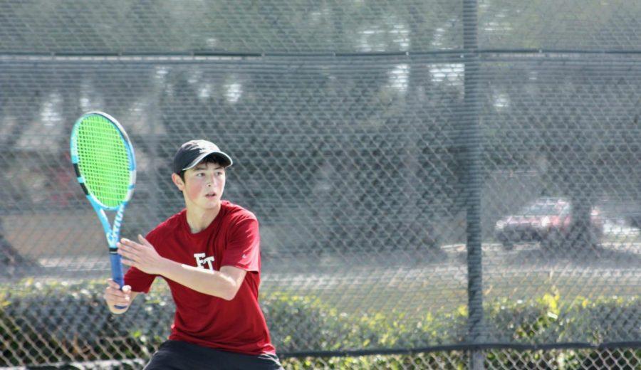 Benjamin Wang 23 raises his racket to intercept the ball.