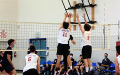 Chase Nielsen '22 and Brayden Jones '22 block the ball from coming over the net.