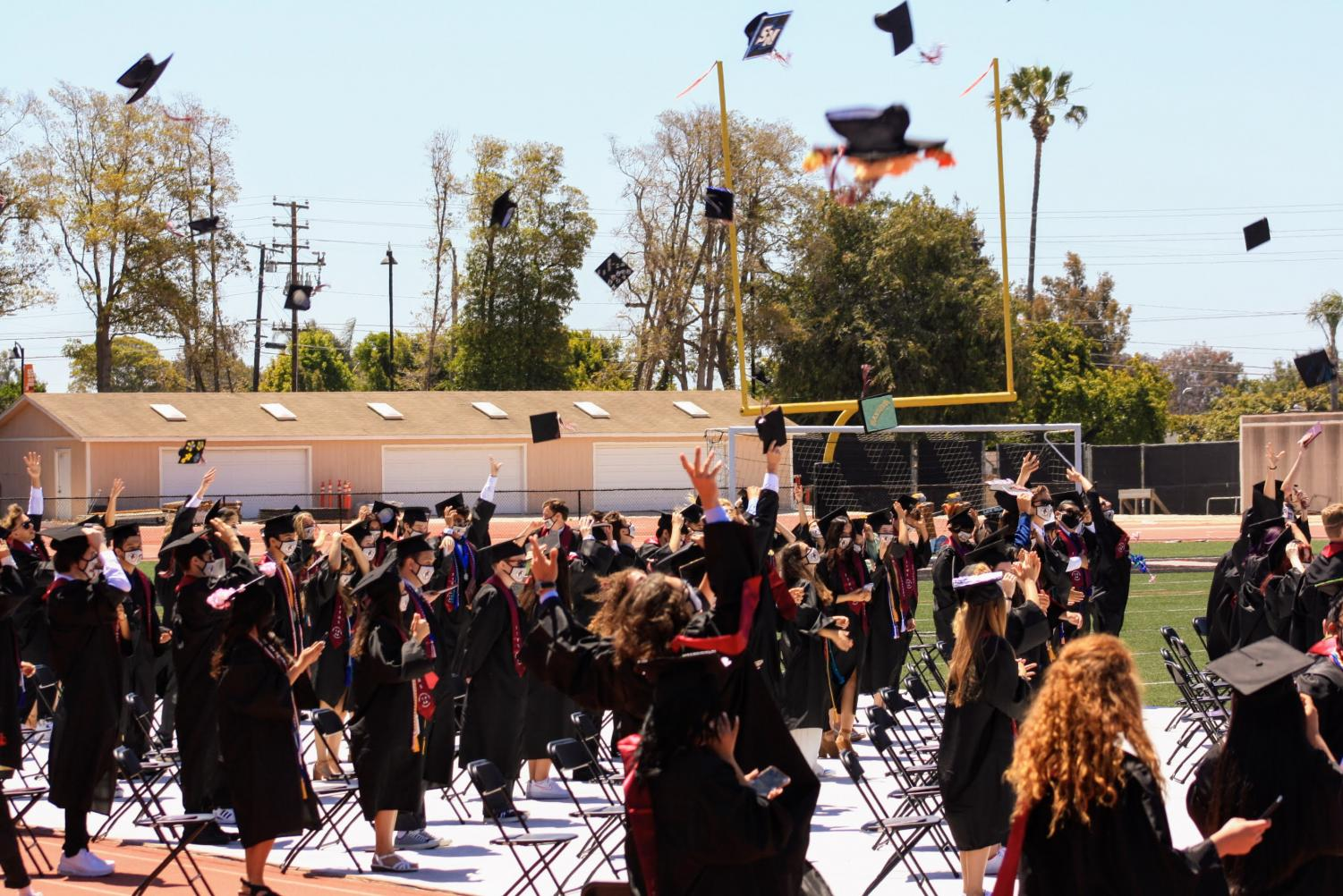 Class of 2021 graduates throw their caps into the air to celebrate the end of their high school experience.