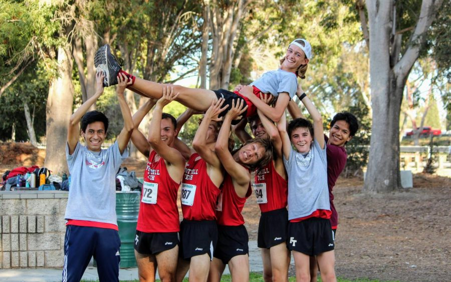 Boys Varsity Cross Country team lifts Jonah Billings 23 into the air in their victory celebration.