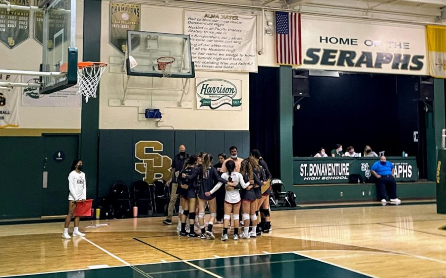 The varsity girls volleyball team huddles during a time out in an attempt to redeem themselves in the game.