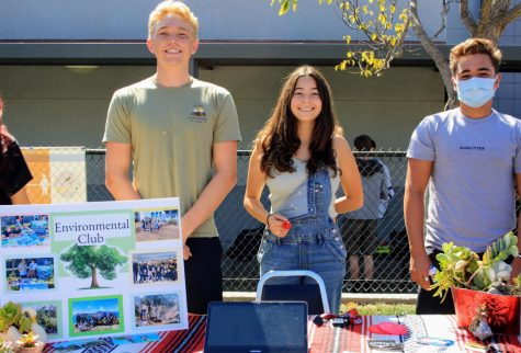 The three representatives for Environmental Club show their passion for the Earth with a poster and plants.