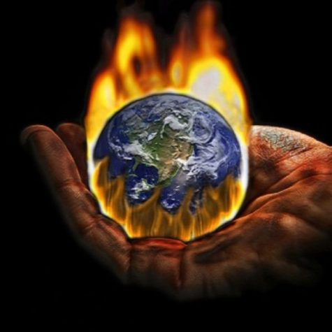 The earth's burning fate lying within the palm of a hand, symbolizing the destruction of human  intervention with our environment.