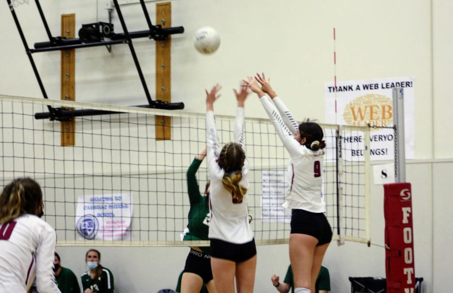 Maliah Juker 22 and Aimee Kidwell 22 block a spike from the opposing team and score a point.